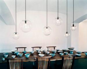 Un esempio di una serie di sospensioni sul tavolo da pranzo, uguali, ma di dimensioni e posizionate ad altezze diverse, creano un piacevole effetto movimentato e azzerano l'effetto-interrogatorio di un unico lampadario.